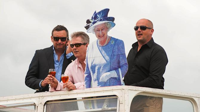 Racegoers are seen with a cardboard cut-out of Queen Elizabeth II during Investec Ladies' Day of the Investec Derby Festival at Epsom Racecourse, Epson, southern England Friday June 1, 2012.  Queen Elizabeth II kicks off a long weekend of celebrations of her 60-year reign by going to the races, and perhaps no other event will give her so much pleasure. The Epsom Derby is the richest event on Britain's horse-racing calendar, and never mind that this is the only major race in which the queen has never entered a winner. Pleasure, in the gilded life of Queen Elizabeth II, often comes on four hooves.  (AP Photo/Dominic Lipinski/PA Wire)  UNITED KINGDOM OUT