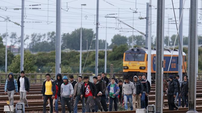 Migrants make their way along train tracks as they attempt to access the Channel Tunnel in Frethun, near Calais