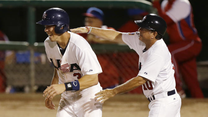 United States' Bradley Zimmer, left, celebrates with assistant coach Tim Esmay, right, after scoring on a RBI single by Matt Chapman in the 11th inning of a 2-1 victory over Cuba in an exhibition baseball game, Thursday, July 18, 2013, in Des Moines, Iowa. (AP Photo/Charlie Neibergall)