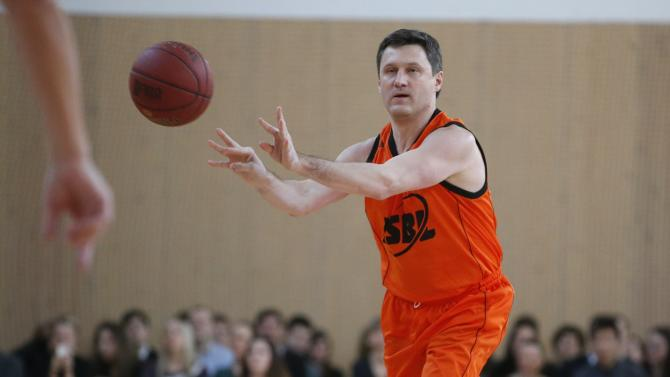 Russia's Energy Minister Novak makes a throw during the basketball match between graduates and students of the Moscow State University in Moscow