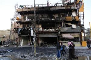 People gather at the site of a bomb attack in Baghdad's Karrada district