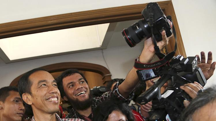 "Indonesian presidential candidate Joko Widodo, popularly known as ""Jokowi"" poses with a photographer for a ""selfie"" photo following a press conference in Jakarta, Indonesia, Thursday, July 10, 2014. Jakarta Governor Joko ""Jokowi"" Widodo and former army general Prabowo Subianto are both claiming victory in Indonesia's presidential election based on unofficial ""quick counts,"" raising the specter of prolonged political instability in Southeast Asia's largest economy. (AP Photo/Tatan Syuflana)"