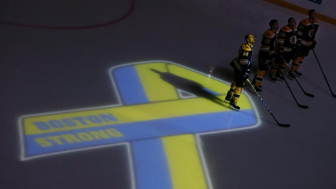 Boston Bruins starters, including defenseman Dennis Seidenberg (44), stand next to a ribbon projected onto the ice at TD Garden in Boston, Wednesday, April 17, 2013, during a ceremony before an NHL hockey game against the Buffalo Sabres in the aftermath of Monday's Boston Marathon bombings. (AP Photo/Elise Amendola)