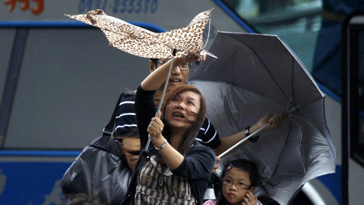A monther and her family brave winds from the approaching Typhoon Saola in Taipei, Taiwan, Wednesday, Aug. 1, 2012. (AP Photo/Wally Santana)