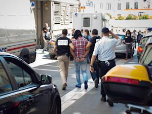One of the two suspects (C) into the murder of 77-year-old heiress Helene Pastor arrives at the Courthouse in Marseille, southeastern France, on June 27, 2014