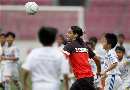 Atletico Madrid's Radamel Falcao runs plays in a mass soccer game with 130 school students in Singapore on Tuesday, May 21, 2013. Atletico Madrid will not stand in the way of striker Falcao if he want