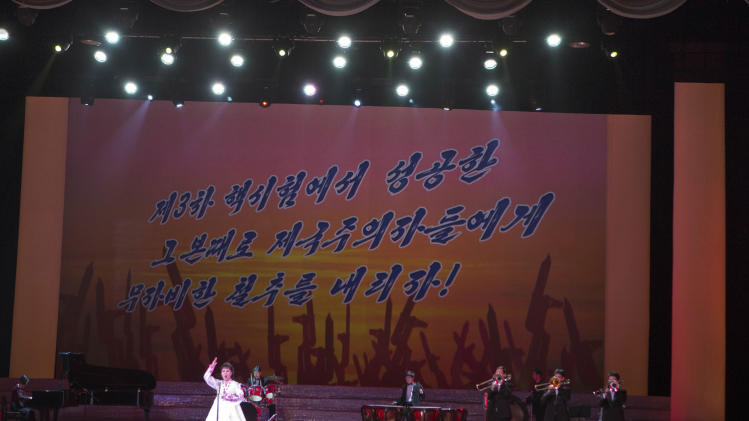 "A North Korean musical performance is held in Pyongyang with  the words ""Let's strike the imperialists mercilessly with the same success we had carrying out the 3rd nuclear test"" projected on a screen, on Sunday, Feb. 17, 2013. (AP Photo/David Guttenfelder)"