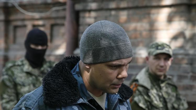 Pro-Russian men escort Dmitry Tomarevsky, who claims he is a member of the Ukrainian far-right group Right Sector, in Slaviansk