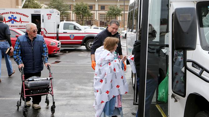Residents of the Wedgwood Senior Apartments are moved to other locations after being evacuated to Churchill High School following a three-alarm fire at the apartments, Sunday, Dec. 28, 2014 in San Antonio, Texas. Five people died after a fire broke out at the senior-living apartment building in the San Antonio suburb of Castle Hills, authorities said. (AP Photo/San Antonio Express-News, Marvin Pfeiffer)