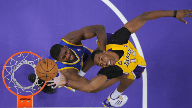Los Angeles Lakers center Dwight Howard, right, puts up a shot as Golden State Warriors center Festus Ezeli, of Nigeria, defends during the first half of their NBA basketball game, Friday, April 12, 2013, in Los Angeles. (AP Photo/Mark J. Terrill)