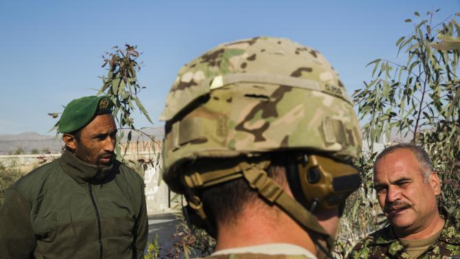 A U.S. soldier from Dragon Company of the 3rd Cavalry Regiment speaks with soldiers in the Afghan National Army during a mission near forward operating base Gamberi in the Laghman province of Afghanistan