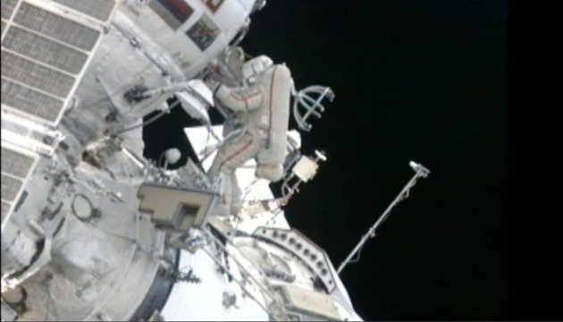 In this still image made from video provided by NASA, a Russian cosmonaut installs shields to protect against zooming pieces of junk to improve the safety of his orbiting home Monday, Aug. 20, 2012. Gennady Padalka and Yuri Malenchenko hung the panels on the Russian side of the International Space Station, after moving a bulky crane and tossing overboard a small spherical satellite on Monday. (AP Photo/NASA)