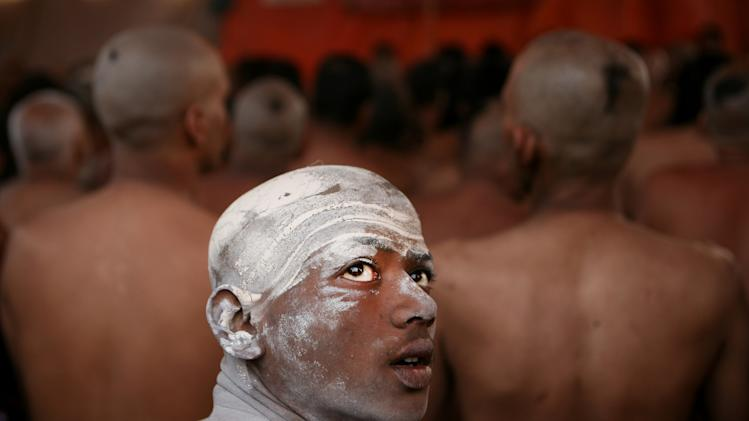 In this Feb. 6, 2013 file photo, a Naga Sadhu, center, watches as other Hindu holy men of the Juna Akhara sect participate in a ritual that is believed to rid them of all ties in this life and dedicate themselves to serving God as a Naga or naked holy men, at Sangam, the confluence of the Ganges and Yamuna River during the Maha Kumbh festival in Allahabad, India. The significance of nakedness is that they will not have any worldly ties to material belongings, even something as simple as clothes. This ritual that transforms selected holy men to Naga can only be done at the Kumbh festival. (AP Photo/ Rajesh Kumar Singh, File)