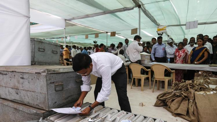 A member of election staff checks the numbers on electronic voting machines at distribution centre ahead of sixth phase of India's general election in Mumbai