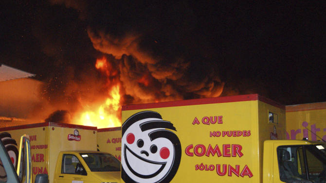 In this photo taken late Friday, May 25, 2012, flames rise from a warehouse of the Mexican potato-chip company Sabritas, in Lazaro Cardenas, Mexico. Over the weekend, unidentified gunmen launched a series of coordinated attacks against the company's installations in the western state of Michoacan in what has been described as the most violent and concerted attack on a private transnational company in the country's 5 ½-year drug war. Sabritas is a subsidiary of PepsiCo. (AP Photo)