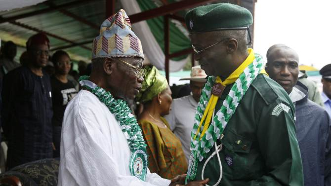 Lagos state governor Babatunde Raji Fashola greets former governor Lateef Jakande after a parade marking Nigeria's 54th Independence Day in Lagos