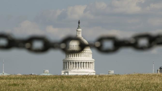 The U.S. Capitol is photographed through a chain fence in Washington