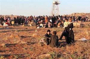 Syrian refugees, fleeing the violence in Syria, wait to enter Turkey on the Syrian-Turkish border in Shamm Alqrain village, northern countryside of Aleppo