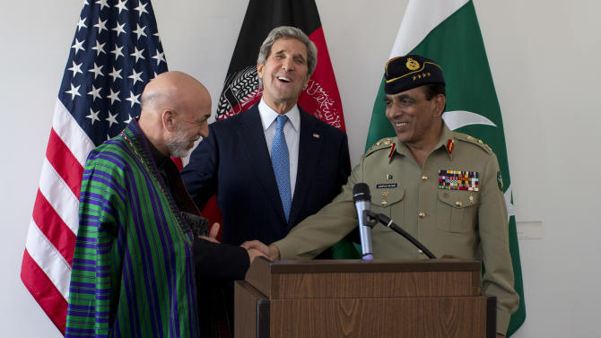 U.S. Secretary of State John Kerry, center, laughs as Afghan President Hamid Karzai, left, and Pakistani Army Chief Gen. Asfhaq Parvez Kayani shake hands after he made a statement after a meeting on Wednesday, April 24, 2013, in Brussels, Belgium. The trilateral meeting is to discuss regional security issues, and the 2014 withdrawal of NATO combat forces from Afghanistan. (AP Photo/Evan Vucci, Pool)