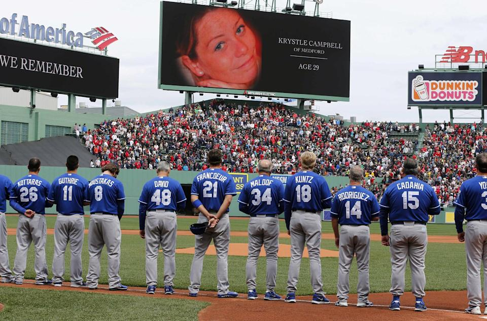 The Kansas City Royals stand during tribute to Boston Marathon bombing victims, including Krystle Campbell, shown on screen, before the Royals' baseball game against the Boston Red Sox in Boston, Saturday, April 20, 2013. (AP Photo/Michael Dwyer)