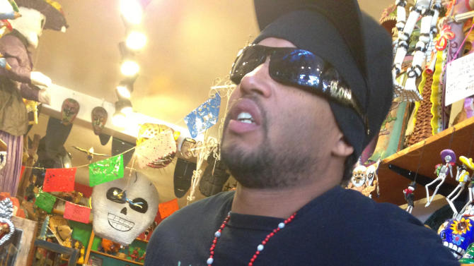 in this Feb. 13, 2013 photo, actor Gregory Beasley Jr., 35, with a La Santa Muerte statue around his neck, is shown at the Masks y Mas art store in Albuquerque, N.M. Beasley is a follower of La Santa Muerte, an underworld saint most recently associated with the violent drug trade in Mexico, but now is spreading throughout the U.S. among a new group of followers ranging from immigrant small business owners to artists and gay activists. In addition to showing up at drug crime scenes, the once-underground icon has been spotted on passion candles in Richmond, Va. grocery stores. (AP Photo/Russell Contreras)