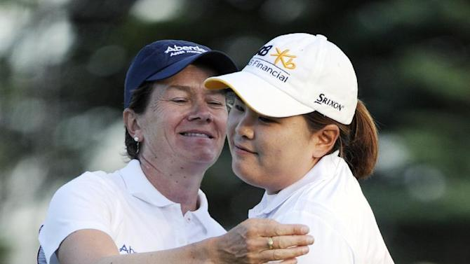 Catriona Matthew, left, of Scotland, hugs Inbee Park, of South Korea, after Park won a sudden death overtime playoff during the LPGA Championship golf tournament at Locust Hill Country Club, in Pittsford, N.Y., on Sunday, June 9, 2013. (AP Photo/Gary Wiepert)