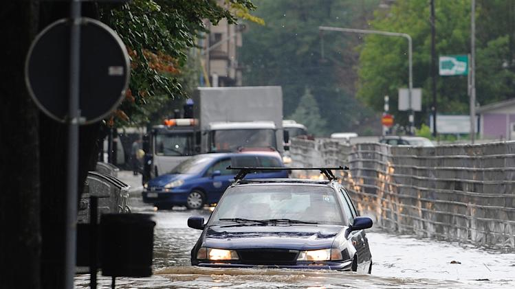 A car drives through a flooded street after a storm in Macedonia's capital Skopje, on Thursday, July 31, 2014. A storm with heavy rain and strong wind engulfed the city flooding the streets and breaking trees. There are no reports of injuries. (AP Photo/Boris Grdanoski)