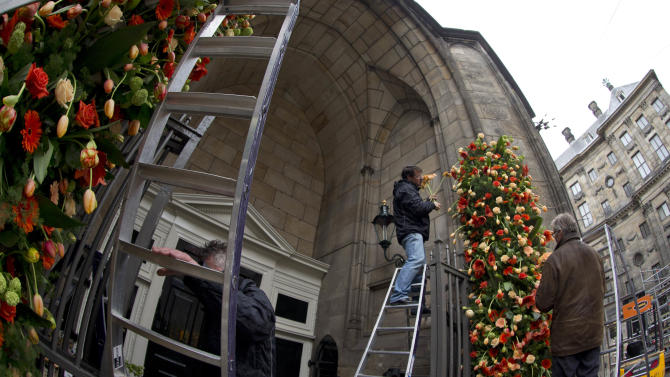 Floral arrangements are made at the entrance of Nieuwe Kerk, adjacent to the Royal Palace, right, in Amsterdam, Netherlands, Monday, April 29, 2013. Netherlands' Queen Beatrix will step down on April 30, 2013, leaving the monarchy to her son Crown Prince Willem Alexander. (AP Photo/Peter Dejong)