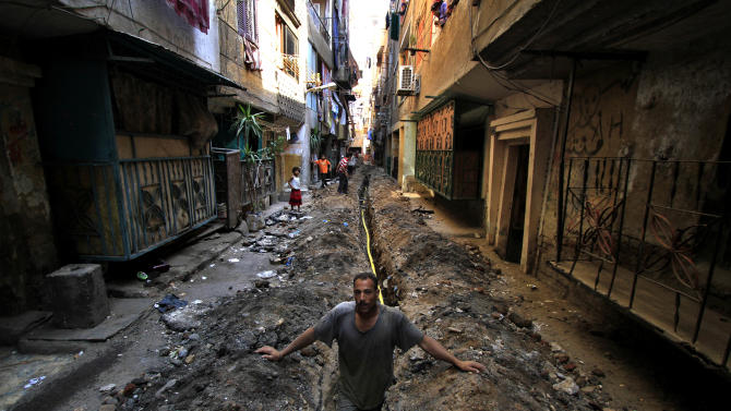 In this July 6, 2011 photo, a worker stands in a ditch for a cooking gas line in an alley in the crowded neighborhood of Mit Oqba in Cairo. All over Egypt, dozens of Popular Committees have sprouted, each dedicated to bringing the can-do spirit of Egypt's revolution to a neighborhood. But the committees are running up against former local officials under the Mubarak regime who still hold considerable power, showing that the old regime is alive and well in the new Egypt. (AP Photo/Khalil Hamra)