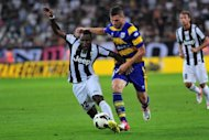 Juventus&#39; midfielder Kwadwo Asamoah (L) clashes with Parma&#39;s defender Aleandro Rosi during their Italian Serie A football match at the &quot;Juventus Stadium&quot; in Turin. Juventus overcame a sluggish first-half display to kick off the defence of their Serie A crown with a 2-0 victory at home to Parma
