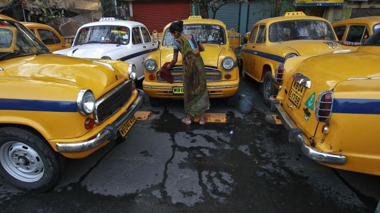 Sumitra Sarkar, 35, cleans a yellow ambassador taxi at a parking area along a roadside in Kolkata