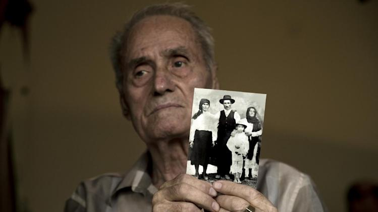 In this July 11, 2014, photo, retired Lt. Col. Alexandru Visinescu poses holding a photograph showing him as a child and the couple, right, that adopted him after his mother Line, left, could no longer afford raising him, at his home in Bucharest, Romania. For the first time since the communism collapsed in Romania 25 years ago, a former prison commander goes on trial Monday, July 14, charged with torturing and murdering prisoners considered a threat to the country's old order. (AP Photo/Vadim Ghirda)