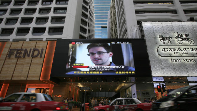 """A TV screen shows a news report of Edward Snowden, a former CIA employee who leaked top-secret documents about sweeping U.S. surveillance programs, at a shopping mall in Hong Kong Sunday, June 23, 2013. The former National Security Agency contractor wanted by the United States for revealing two highly classified surveillance programs has been allowed to leave for a """"third country"""" because a U.S. extradition request did not fully comply with Hong Kong law, the territory's government said Sunday. (AP Photo/Vincent Yu)"""