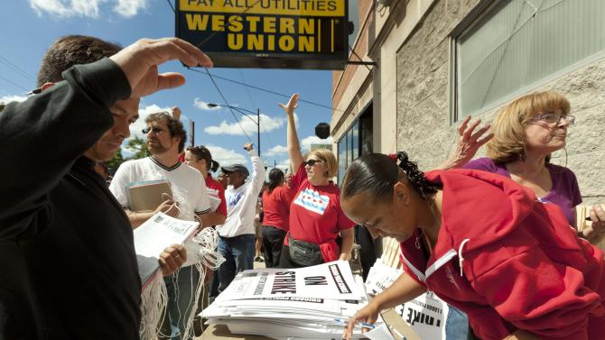 Teachers respond enthusiastically to passing drivers honking their horns in support as they distribute strike signage at the Chicago Teachers Union strike headquarters on Saturday, Sept. 8, 2012 in Chicago. The union has vowed to strike on Monday, Sept. 10, 2012, should it fail to reach an agreement over teachers' contracts with Chicago Public Schools by  that date. (AP Photo/Sitthixay Ditthavong)