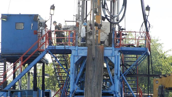 FILE - In a Monday, June 25, 2012 photo, a crew works on a drilling rig at a well site for shale based natural gas in Zelienople, Pa. .S. consumer prices rose slightly in May 2013, as higher energy costs were partly offset by cheaper food. The small increase underscores that inflation is mild. (AP Photo/Keith Srakocic, File)