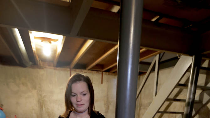 Crystal Anderson stands in her basement Thursday, Feb. 7, 2013, in Kansas City, Mo. On Monday, police rescued a 17-year-old boy who had been handcuffed to a post in the neighbor's basement after receiving a tip from Anderson. (AP Photo/Charlie Riedel)