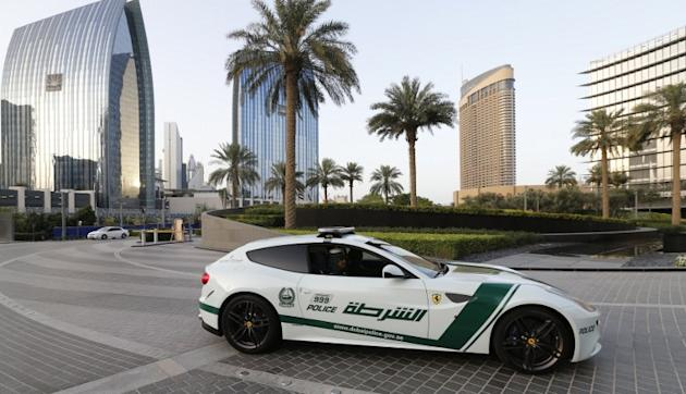 Emirati female police officers drive a Ferrari police vehicle in the Gulf emirate of Dubai on April 25, 2013. Dubai police showed off a new Ferrari they will use to patrol the city state, hot on the h