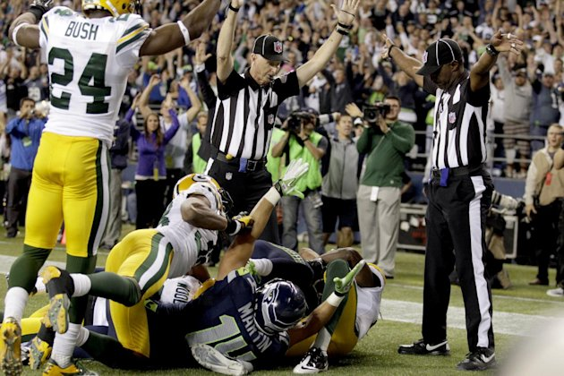 Sept. 24 FILE - In this Sept. 24, 2012, file photo, an official, rear center, signals for a touchdown by Seattle Seahawks wide receiver Golden Tate, obscured, as another official, at right, signals a