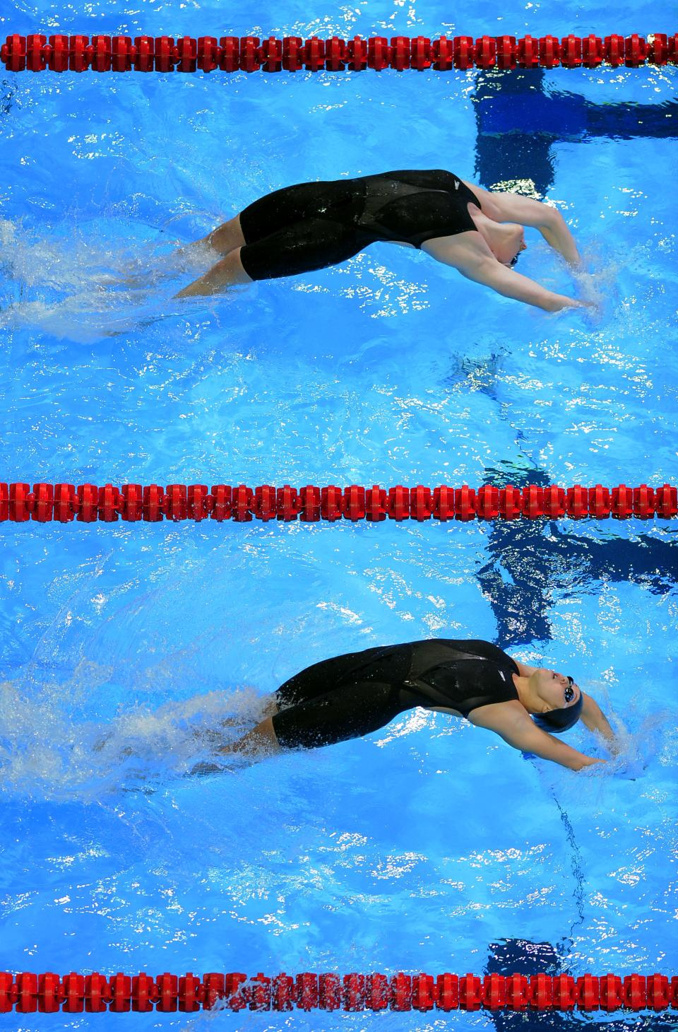 Jennifer Connolly and Rachel Bootsma, from top, start in the women's 100-meter backstroke preliminaries at the U.S. Olympic swimming trials, Tuesday, June 26, 2012, in Omaha, Neb. (AP Photo/Mark J. Terrill)
