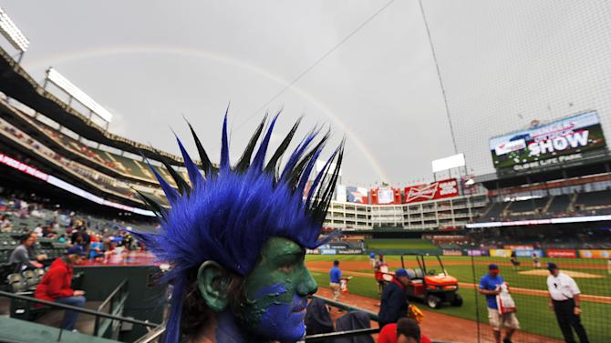 A rainbow arcs over Matt Stixrud's mohawk as ground crews prepare a wet field before the start of the first inning of a baseball game between the Texas Rangers and Seattle Mariners, Monday, April 27, 2015, in Arlington, Texas. (AP Photo/Brandon Wade)