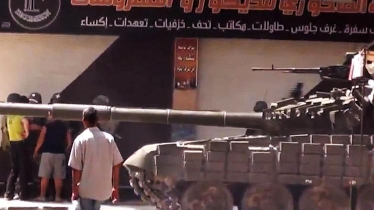 This image made from amateur video released by Shaam News Network and accessed Tuesday, July 31, 2012, purports to show a man walking past Syrian a military tank in Damascus, Syria. (AP Photo/Shaam News Network via AP video) THE ASSOCIATED PRESS IS UNABLE TO INDEPENDENTLY VERIFY THE AUTHENTICITY, CONTENT, LOCATION OR DATE OF THIS HANDOUT PHOTO