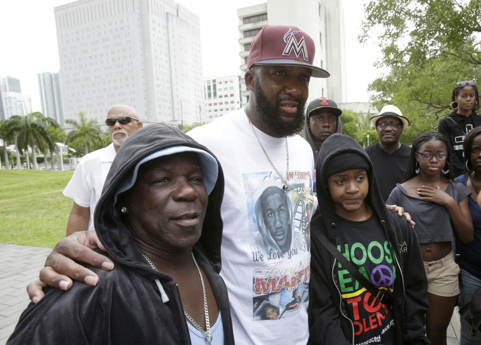 "Tracy Martin, center, father of Trayvon Martin, poses for photos with supporters wearing hoodies, at a ""Justice for Trayvon"" rally, Saturday, July 20, 2013 in Miami, one week after George Zimmerman was found not guilty in the shooting death of unarmed teenager Trayvon Martin. (AP Photo/Wilfredo Lee)"