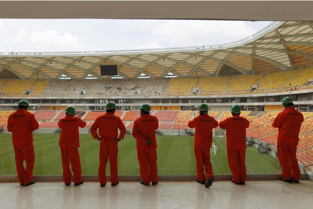 Construction workers look out over the Arena Amazonia stadium in Manaus