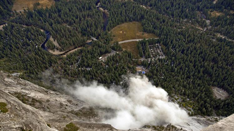 FILE - In this Oct. 8, 2008, file photo, a dust cloud is seen from the Glacier Point overlook during a rock fall that damaged lodging facilities at Curry Village in Yosemite National Park, Calif. Falling boulders are the single biggest force shaping Yosemite Valley, one of the most popular tourist destinations in the nation's system of national parks. Now large swaths of popular haunts deemed unsafe are closing as officials acknowledge they knew for more than a decade ago that unsuspecting tourists were being lodged in harm's way. On Thursday, June 14, 2012,  the National Park Service will announce that potential danger from the unstable 3,000-foot-tall slab of granite known as Glacier Point, a picturesque promontory that for decades has provided a dramatic backdrop to park entertainment events, will leave uninhabitable large parts of Yosemite Valley's most popular lodging areas. (AP Photo/Jim Nichols, File)
