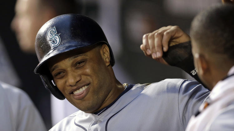 Seattle Mariners' Robinson Cano high-fives teammates in the dugout after scoring on a double by Kendrys Morales in the fourth inning of a baseball game against the Baltimore Orioles, Friday, Aug. 1, 2014, in Baltimore. (AP Photo/Patrick Semansky)