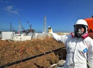 "A journalist checks the radiation level with her dosimeter at the Fukushima Dai-ichi nuclear power plant in February 2012. The Fukushima nuclear accident was a man-made disaster caused by Japan's culture of ""reflexive obedience"" and not just the tsunami that hit the plant, according to a damning parliamentary report"