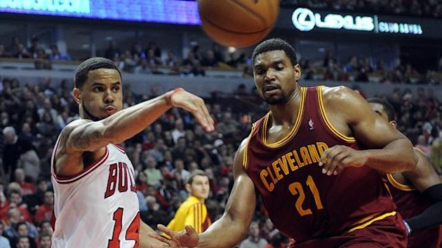 Chicago Bulls point guard D.J. Augustin (14) passes the ball around Cleveland Cavaliers center Andrew Bynum (21) during the second half at the United Center (Reuters)