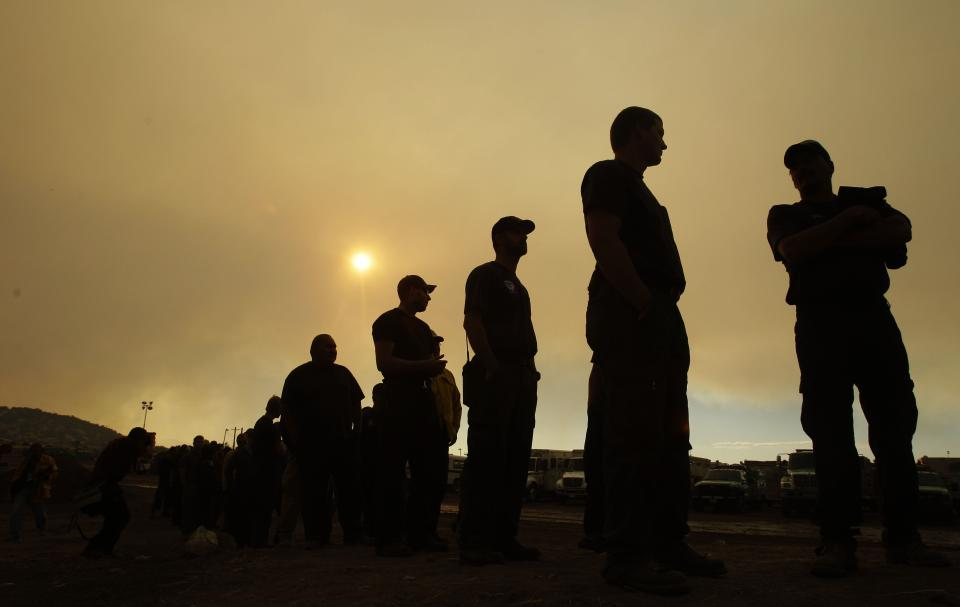 Firefighters line up for a meal as smoke from the Wallow Fire fills the sky at an incident command center in Eagar, Ariz., Thursday, June 9, 2011. (AP Photo/Marcio Jose Sanchez)