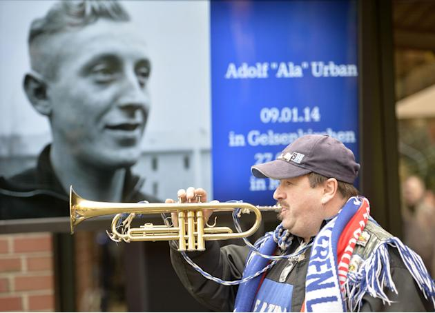 A Schalke fan plays a trumpet in front of a picture of Adolf Urban, a storied player for soccer club FC Schalke 04 who was killed in Eastern Front fighting in World War II and  and who is being reburi