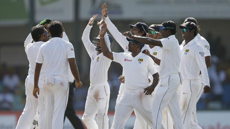 Sri Lanka's cricket team members celebrate the dismissal of South Africa's captain Amla during the fifth and final day of their second test cricket match in Colombo